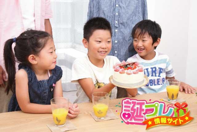 3人の子供とバースデーケーキの画像